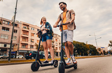 Young Couple On Vacation Having Fun Driving Electric Scooter Through The City.