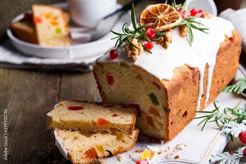Tuinposter Brood Fruit cake dusted sliced with icing, nuts, kernels pomegranate and dry orange close-up. Christmas and Winter Holidays homemade cake