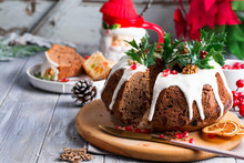 Christmas Sliced Chocolate Cake With White Icing, Holly Branches And Pomegranate Kernels On A Gray Wooden Background