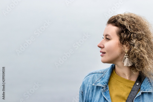 Portrait of a young woman with curly hair looking away dreaming, outdoors, profile view Wallpaper Mural