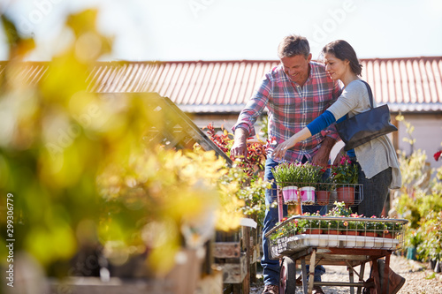 Mature Couple Pushing Trolley With Plants They Have Bought At Garden Center - 299306779