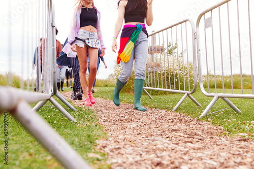 Close Up Of Friends At Entrance To Music Festival Walking Through Security Barriers - 299307961