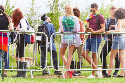 Fotografía  Group Of Young Friends Waiting Behind Barrier At Entrance To Music Festival Site