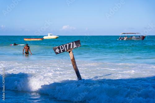 Montage in der Fensternische Sansibar Pointer pizza on a wooden post in sea water on the tropical beach of Zanzibar island, Tanzania, Africa. Travel and vacation concept