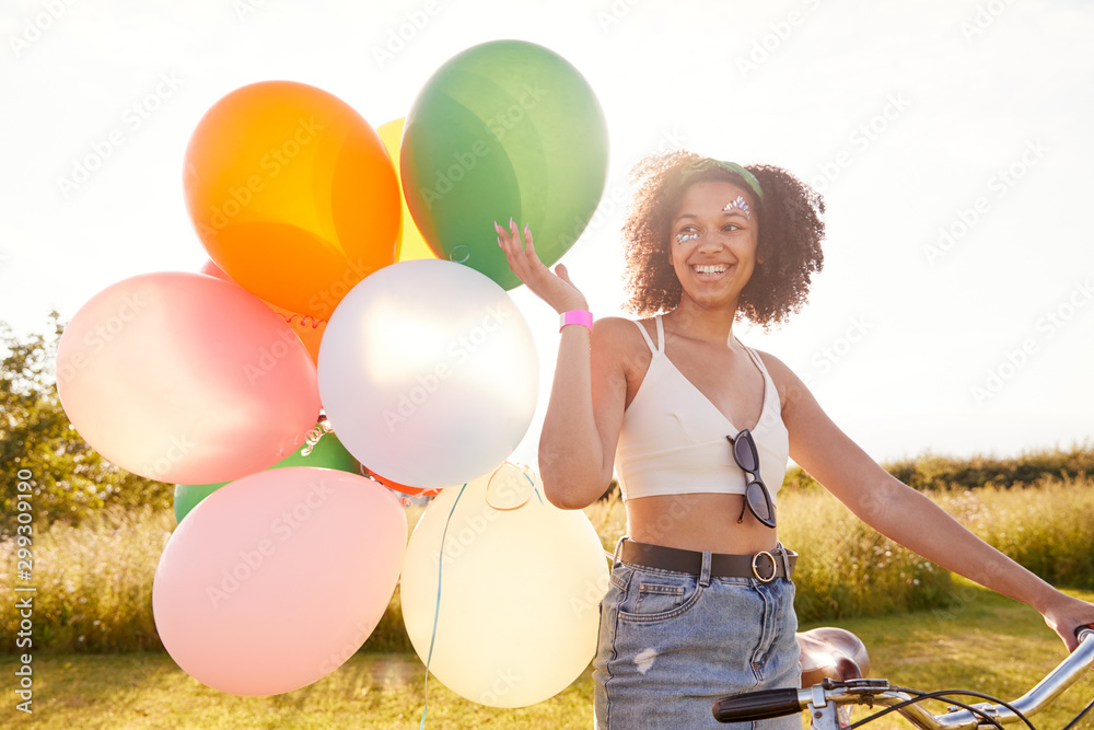 Fototapeta Young Woman Riding Bicycle Decorated With Balloons Through Countryside Against Flaring Sun