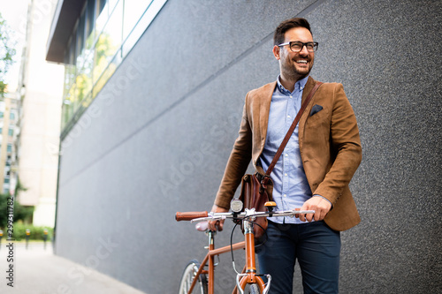 obraz dibond Happy young stylish businessman going to work by bike