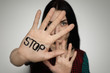 Young woman with word STOP written on her palm against light background, focus on hand