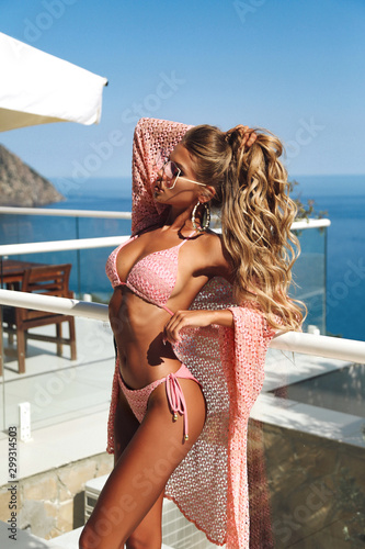 Fototapeta sexy woman with blond hair in elegant swimming suit posing near open air swimmin