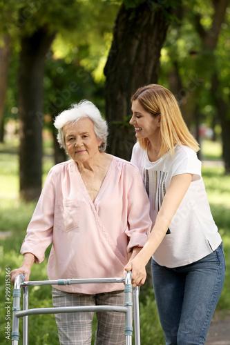 Montage in der Fensternische Lineale Wachstum Caretaker helping elderly woman with walking frame outdoors