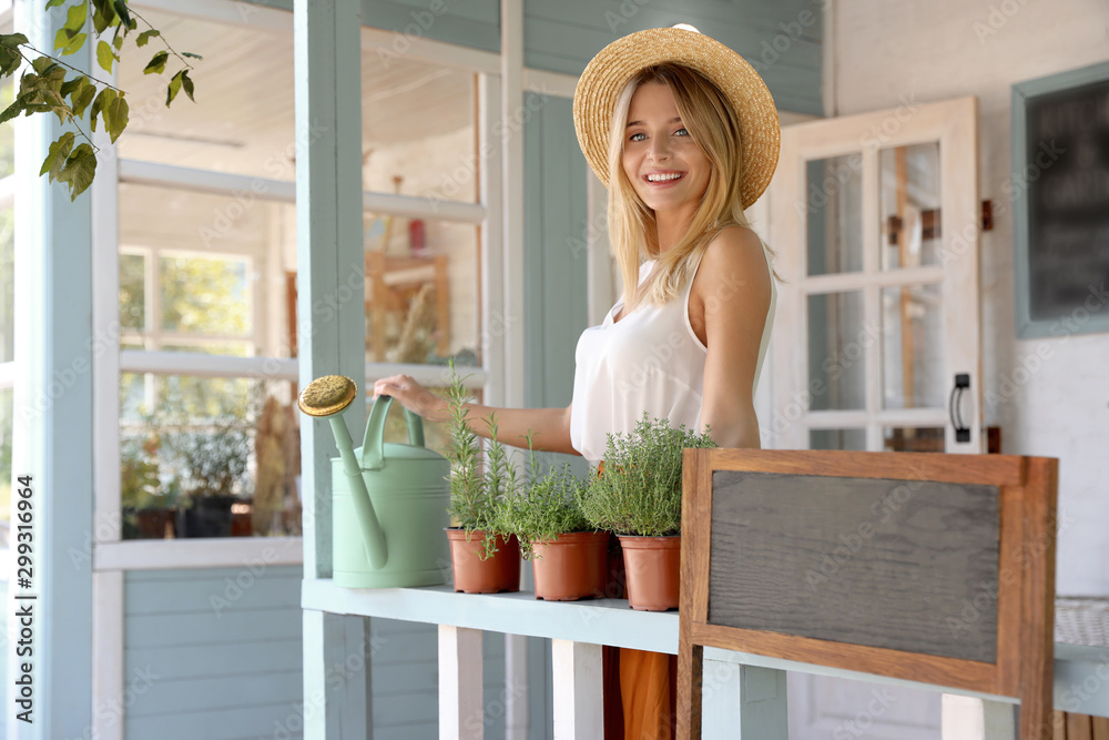 Fototapety, obrazy: Young woman with watering can and home plants on veranda, space for text