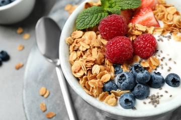 Tasty homemade granola with yogurt and berries on grey table, closeup. Healthy breakfast