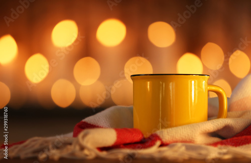 Fototapeta Cup of hot drink on scarf against blurred background. Winter atmosphere obraz