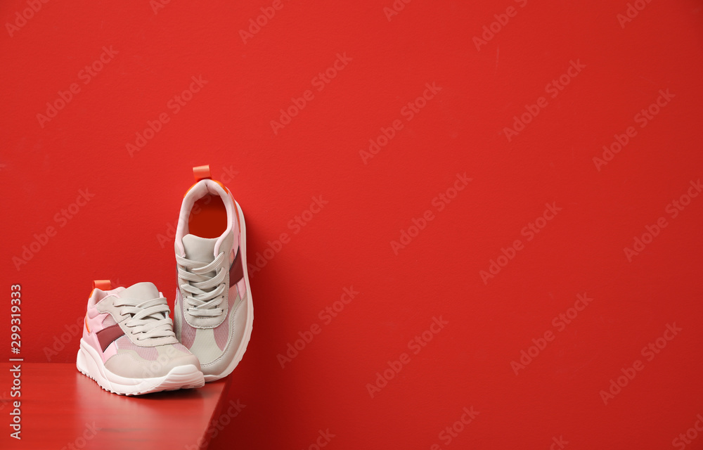 Fototapety, obrazy: Stylish women's sneakers on wooden table near red wall, space for text