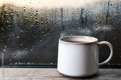 Obraz Cup of hot tea on wooden window sill. space for text. Rainy weather - fototapety do salonu