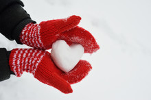 Female Hands In Warm Red Crocheted Mittens With Snowy Heart. White Snow Background. Love Concept. Valentine's Day Greeting Card With Copyspace