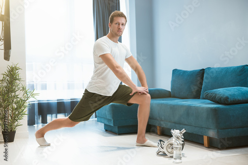 Photo young handsome man doing lunges during stretching before workout at home looking