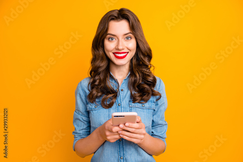 Fototapeta Photo of trendy cheerful cute nice sweet pretty girl smiling toothily holding phone with hands expressing positive reaction to received messages isolated over yellow vivid color background obraz