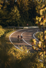 Cyclists On A Windy Mountainroad In Upper Franconia At Sunset