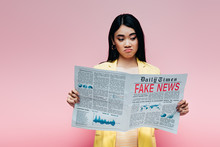 Upset Asian Woman In Yellow Outfit Reading Newspaper With Fake News Isolated On Pink