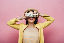 Asian Woman Holding Wooden Cubes In Front Of Face With Fake And Fact Lettering Isolated On Pink