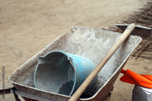 The wheelbarrow in the yard to work the cement with bucket and shovel Fototapet