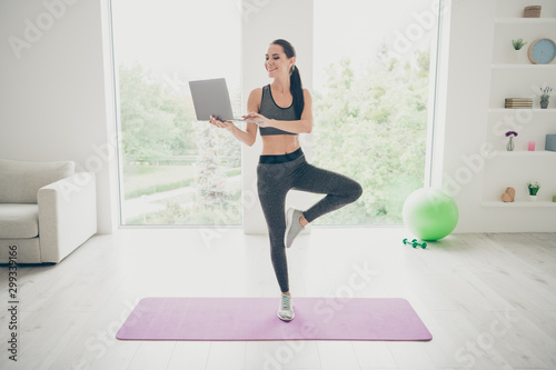 Obraz Full size photo of positive charming sportive girl work computer search films movies about doing sport exercise doing crossfit wellbeing warm-up standing on violet mat in studio house gym - fototapety do salonu