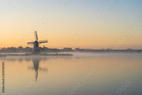 Canvas Print Nature awakens at a traditional Dutch windmill during a foggy dawn