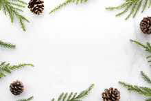 White Marble Table With Christmas Decoration Including Pine Branches And Pine Cones. Merry Christmas And Happy New Year Concept. Top View With Copy Space, Flat Lay.