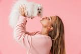 Fototapeta Zwierzęta - Beautiful lovely girl holding her pet lapdog