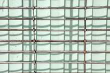 A Storefront Metal Security Gate Creates A Shadow Grid In The Bright Sunlight.