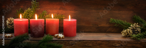 Fototapeta Fourth  Sunday in Advent, four burning red candles in a row, fir branches and Christmas decoration on dark rustic wood, wide panoramic format with copy space obraz