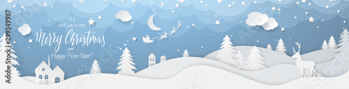 Fototapeta Winter landscape with deer paper cut-out and fir trees in snow. Festive horizontal banner with text Merry Christmas, Village and flying santa's sleigh in night sky with stars, snowfall and moon. obraz