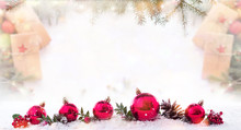 Christmas Card, New Year's Balls On Snow. Fir Branches And Gift Packages In Bokeh Background