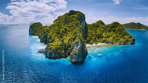 obraz lub plakat Aerial drone panorama view of tropical paradise island. Karst limestone rocky mountains surrounds by blue ocean and coral reef