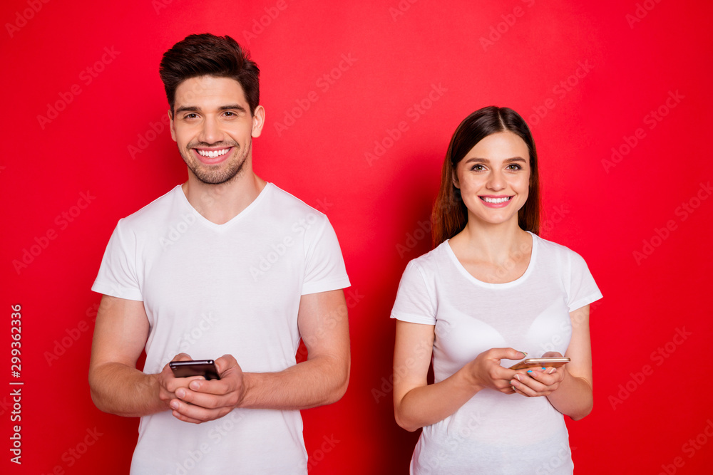 Fototapeta Photo of cheerful positive nice cute pretty couple of two people chatting with each other via telephones smiling toothily beaming in white t-shirts isolated vivid color background