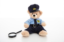 Cute Teddy In Policeman Uniform And Magnifier Isolated Against White Background