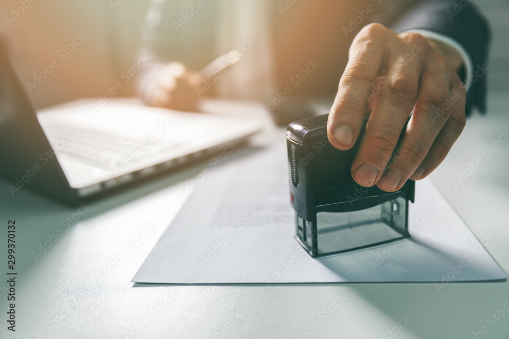 Fototapeta businessman put a stamp on business contract in office
