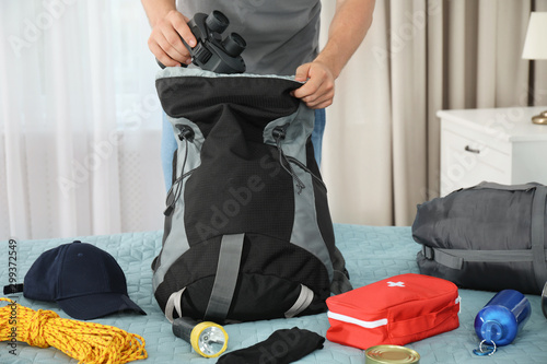 Photo Man packing different camping equipment into backpack at home, closeup