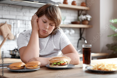 Pinturas sobre lienzo  Emotional overweight boy at table with fast food in kitchen