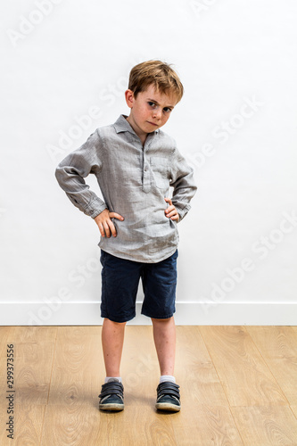 sulking conflicted boy standing with hands on hips expressing attitude
