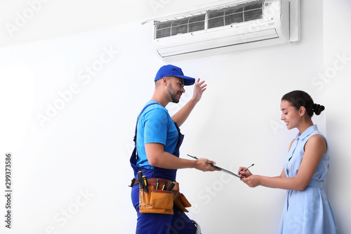 Valokuvatapetti Professional technician speaking with woman about air conditioner indoors