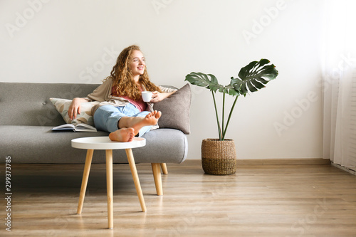 Curly haired brunette woman relaxing on the couch at home.