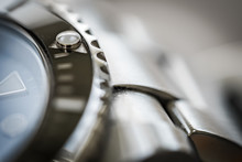 Extreme Close-up Of The Rotating Bezel And Hour Marker Seen On An Iconic, Swiss-made Divers Watch. Part Of The Watch Crystal And Steel Links Are Visible.