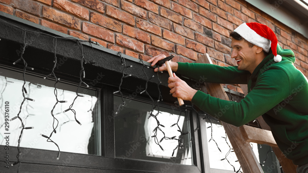 Fototapety, obrazy: Man in Santa hat decorating house with Christmas lights outdoors