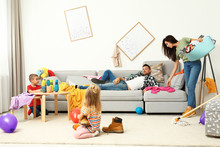 Exhausted Mother Trying To Clean Up Mess Made By Children And Lazy Father In Room
