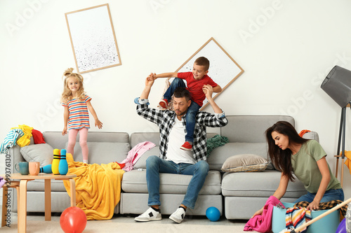 Fényképezés Frustrated mother trying to clean up mess while father playing with children in
