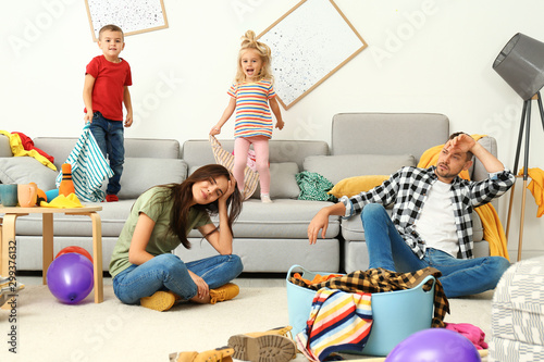 Foto Frustrated parents and their mischievous children in messy room