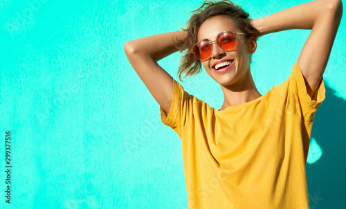 Cuadros en Lienzo Fashionable cheerful young woman posing on blue background, wearing yellow t-short and trendy red eyeglasses