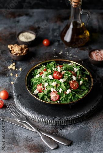 Healthy vegetable salad with fresh arugula, tomato, feta cheese and walnut on dark plate Wallpaper Mural