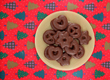 Spiced German Biscuits With Chocolate. In Shape Of Pretzel, Hearts And Stars Christmas Cookies On Red Tablecloth With The Motif Of Festive Trees. Background For Copy Space.